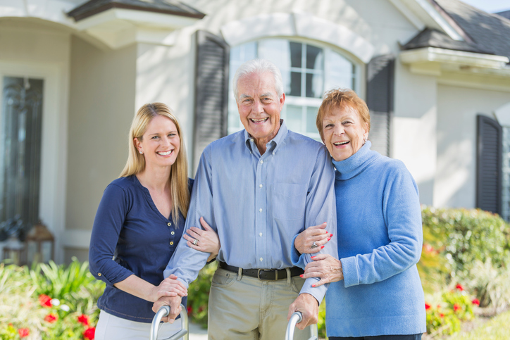 Woman with elderly parents standing in front of a custom home in vancouver wa
